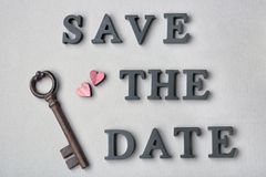 Vintage key and phrase SAVE THE DATE composed with letters on grey background royalty free stock photography