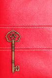 Vintage key on red leather Stock Photo