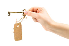 Vintage key with a tag in a female hand Royalty Free Stock Image