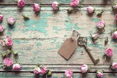 Vintage key with a tag and a little pink roses on an old wooden Stock Image