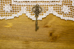 Vintage key on the white aged lace Stock Photography