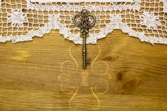 Vintage key on the white aged lace Stock Image