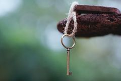 Vintage key with wooden home keyring hanging on old wood plank with blur green garden background, copy space. Property concept stock images