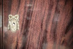 Vintage keyhole with key on vintage wooden cabinet. For background stock images