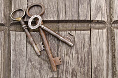 Vintage keys on old wooden background. Close-up. Three old, rustic keys on the table Stock Photo