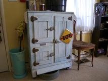 Vintage kitchen with icebox. Vintage kitchen with wooden icebox old chair and cleaning utensils Royalty Free Stock Images