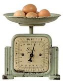 Vintage kitchen-scales with eggs. Antique kitchen-scales with brown eggs isolated on white Royalty Free Stock Image