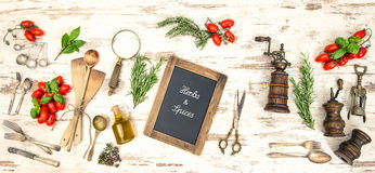 Vintage kitchen utensils with red tomatoes and herbs Royalty Free Stock Images