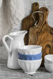 Vintage kitchenware - ceramic bowls, enamelled jug and cutting boards olive Royalty Free Stock Photography
