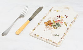 Vintage a knife a fork on a wooden board Stock Photos