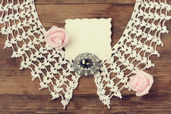 Vintage knitted collar, antique brooch, pink roses, paper card. On wooden table, retro style background Stock Images