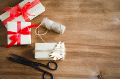 Vintage kraft boxes with gifts, tied with red ribbons and jute with wooden christmas tree on rustic background. Stock Image