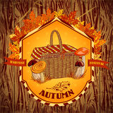 Vintage label autumn harvest festival with mushrooms, basket, autumn leaves and grass on a wooden background. Retro vector illus Stock Photos