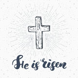 Vintage label, Hand drawn Christian cross with religious sign lettering He is risen, crucifix symbol grunge textured retro badge,. Typography design t-shirt royalty free illustration