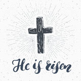 Vintage label, Hand drawn Christian cross with religious sign lettering He is risen, crucifix symbol grunge textured retro badge, Stock Photos