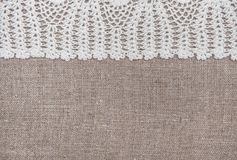 Vintage lace fabric border on the old burlap textile. Background stock photo