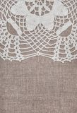 Vintage lace fabric border on the old burlap textile. Background royalty free stock photography