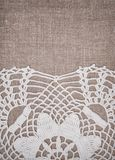 Vintage lace fabric border on the old burlap textile. Background royalty free stock photo