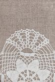 Vintage lace fabric border on the old burlap textile. Background stock image