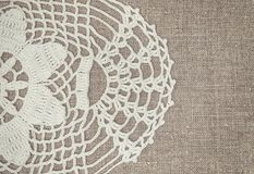 Vintage lace fabric border on the old burlap textile. Background stock photography