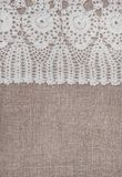 Vintage lace fabric border on the old burlap textile. Background stock images