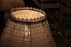 Vintage lace lampshade closeup in darkness. Shabby chic lamp decor. Retro lamp decorated with ornate lace and patterned ribbons. stock photos