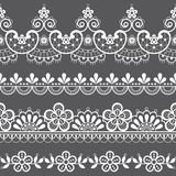 Vintage lace seamless vector pattern, ornamental repetitive design with flowers and swirls in white on gray background royalty free illustration
