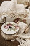 Vintage lace trims and sewing items. Vintage cotton lace trims on wooden spools and sewing items lying on the table royalty free stock image