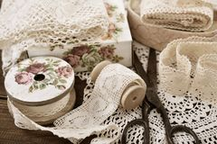 Vintage lace trims and sewing items. Vintage cotton lace trims on wooden spools and sewing items lying on the table stock photo