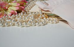 Vintage ladies accessories. Vintage pearls, gloves,purse and flowers royalty free stock images