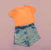 Vintage ladies denim shorts and bright shirt. Stock Photo