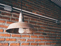 Vintage lamp against brick wall. Close up vintage lamp hanging from red brick wall Royalty Free Stock Photo