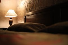 A vintage lamp beside a bed Stock Photos