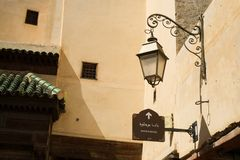 A vintage lamp hanging on the wall near Bab Boujloud sign in Fes el Bali. stock photography