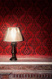 Vintage lamp on old fireplace in room with red rocco pattern Stock Photo