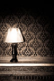 Vintage lamp on old fireplace in room with red rocco pattern Royalty Free Stock Photography