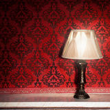 Vintage lamp on old fireplace in room with red rocco pattern Royalty Free Stock Photos