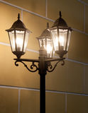 Vintage lamp post. Urban street night scene: vintage streetlamp (lamp post) in front of yellow wall in Saint-Petersburg (Russia) by night (evening). Can be used Royalty Free Stock Photos