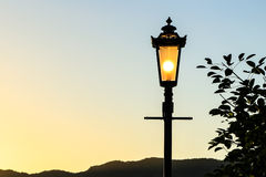 Vintage lamp post with sunset Background (sillhouette) Stock Photo