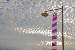 Vintage lamp on top of bamboo pole and pink lanna flagTung on the many cloud in the morning stock image