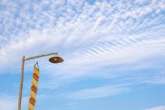 Vintage lamp on top of bamboo pole and yellow lanna flagTung on the blue sky in the morning stock images