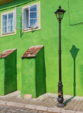 Vintage lamppost in front of green building. Royalty Free Stock Images