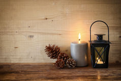 Vintage Lantern with burning Candle and pine cones on wooden table. filtered image Stock Photos