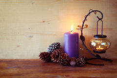 Vintage Lantern with burning Candle and pine cones on wooden table. filtered image. Stock Photography