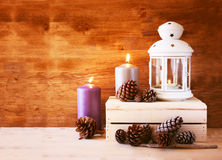 Vintage Lantern with burning Candle and pine cones on wooden table. filtered image Royalty Free Stock Photos