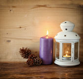 Vintage Lantern with burning Candle and pine cones on wooden table. filtered image. Stock Photo