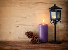 Vintage Lantern with burning Candle and pine cones on wooden table. filtered image Stock Image