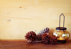 Vintage Lantern with burning Candle and pine cones on wooden table. filtered image Stock Images