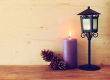 Vintage Lantern with burning Candle and pine cones on wooden table. filtered image. Stock Images