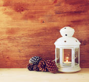 Vintage Lantern with burning Candle and pine cones on wooden table. filtered image. Stock Image